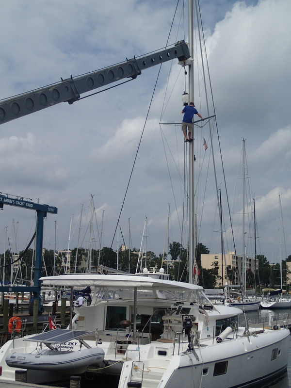 Look Ma, no safety belt, just riding the hoist up the mast